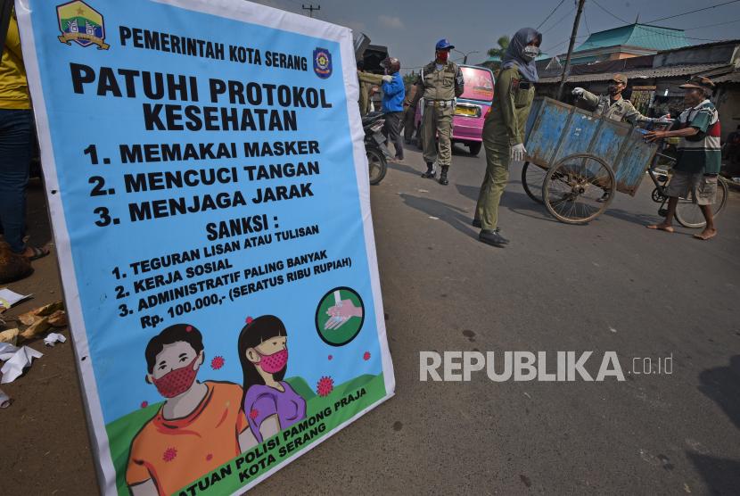 Petugas Satpol PP menegur warga yang tidak memakai masker saat melintas di tempat umum.