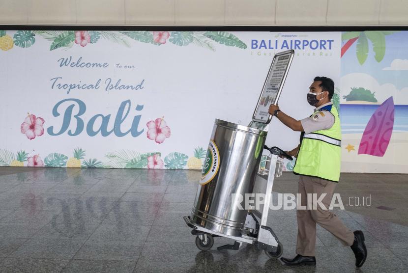Seorang petugas karantina berjalan di area kedatangan internasional selama pembukaan bandara Internasional Ngurah Rai di Bali, Indonesia, 14 Oktober 2021.