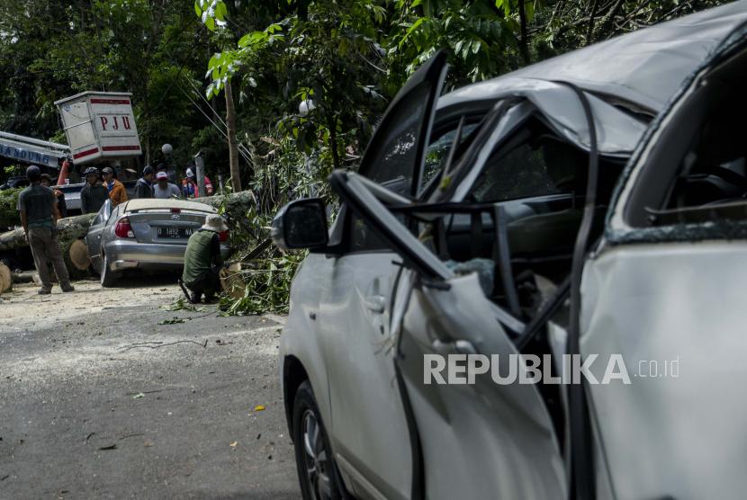 Petugas Dinas Perumahan dan Kawasan Permukiman Pertanahan dan Pertamanan (Dpkp3) Kota Bandung mengevakuasi pohon tumbang yang menimpa mobil di Bandung, Jawa Barat, Kamis (8/4/2021).