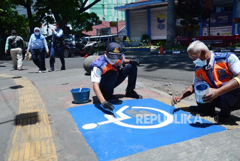Petugas Dishub Kota Bandung, memperbarui tanda untuk penyandang difabel yang telah usang di trotoar Jalan Purnawarman, Kota Bandung, Rabu (22/9). Menjelang peringatan Hari Jadi ke-211, Kota Bandung terus berbenah, termasuk infrastruktur untuk penyandang disabilitas sebagai upaya mewujudkan Bandung sebagai kota ramah disabilitas.