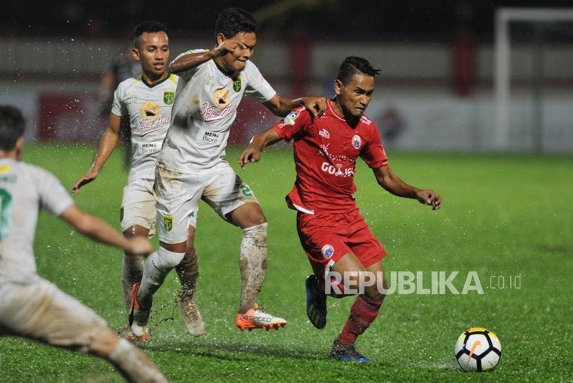 Gelandang Persija Jakarta Ramdani Lestaluhu berusaha melewati hadangan pemain Persebaya dalam laga lanjutan Liga 1 2018 di Stadion PTIK, Jakarta Selatan, Selasa (26/6).