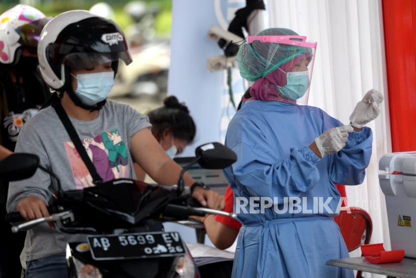 Tenaga kesehatan bersiap menyuntikkan vaksin Covid-19 dari dalam mobil di Area Parkir Sendratari Ramayana, Prambanan, Sleman, Yogyakarta, Senin (5/4). Vaksinasi ini menyasar pelaku usaha pariwisata, pelayan sektor publik, dan tenaga transportasi. Jumlah sasaran vaksin sebanyak 5 ribu orang.
