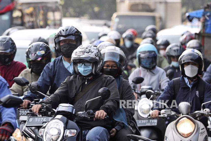 Pengemudi yang memakai masker untuk meredam penyebaran wabah virus corona melewati jam sibuk lalu lintas di Jakarta, Indonesia. Dinkes DKI Jakarta mencatat kepatuhan penggunaan masker turun menjadi hanya 30 persen.