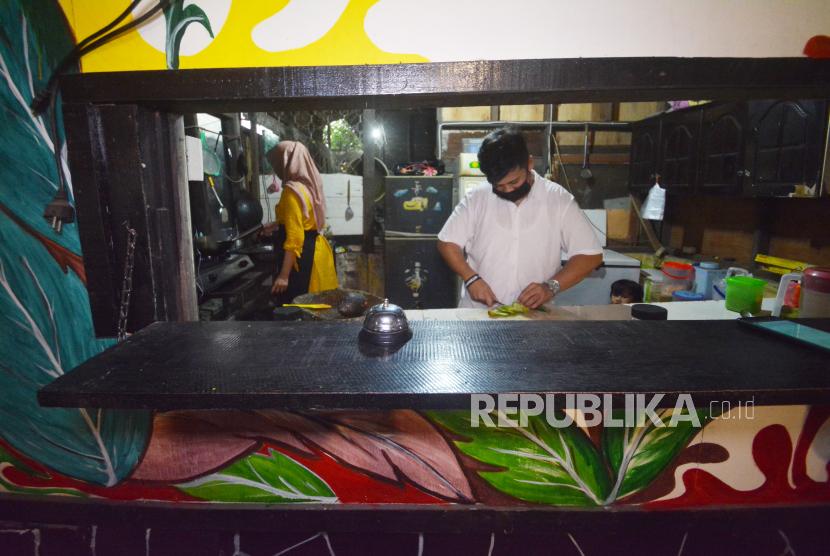 Pelaku usaha kuliner, Adityo Nugraha (25), memasak makanan pesanan konsumen, di kafenya di Padang, Sumatera Barat, Selasa (25/5/2021).  Adityo yang merupakan nasabah PT Pegadaian (Persero) memanfaatkan pinjaman kredit ultra mikro untuk membantu melanjutkan bisnis kafernya yang sepi sejak pandemi