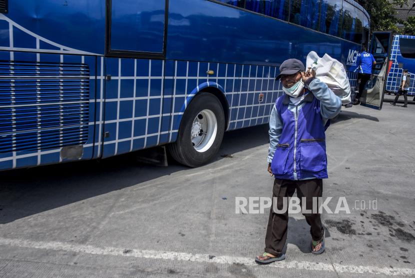 Seorang pelaku transportasi darat berjalan membawa sembako usai kegiatan pemberian bantuan sosial (bansos) bagi pelaku usaha transportasi darat.