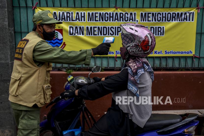 Petugas Linmas memeriksa suhu tubuh warga saat pemberlakuan mini lockdown di Jalan Kademangan, Kelurahan Setiamanah, Kota Cimahi, Senin (5/10/2020).