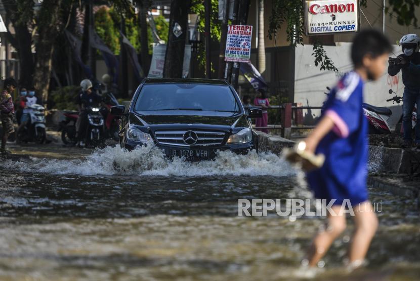 Kendaraan melintasi banjir di Jalan Pramuka, Depok, Jawa Barat, Kamis (23/9). Banjir tersebut akibat sampah yang menumpuk di aliran Kali Licin yang terdapat di kolong jembatan jalan perempatan Mampang, Depok.  Republika/Putra M. Akbar