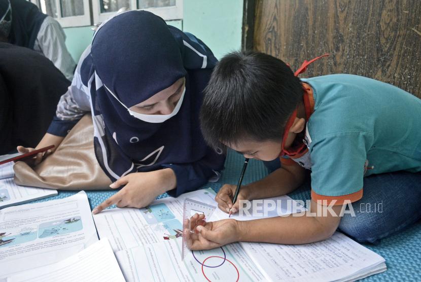 Relawan pendidikan mendampingi siswa SDN Cisero 1 saat kegiatan belajar mengajar di Cisurupan, Kabupaten Garut, Jawa Barat, Kamis (12/11/2020).