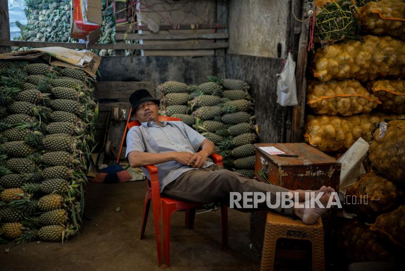 Pedagang tertidur saat menunggu pembeli di lapaknya di Pasar Induk Kramat Jati, Jakarta Timur, Rabu (28/7). Sejumlah pedagang mengaku mengalami penurunan pendapatan sebesar 30 hingga 50 persen imbas dari pembatasan mobilitas kegiatan masyarakat pada masa PPKM.