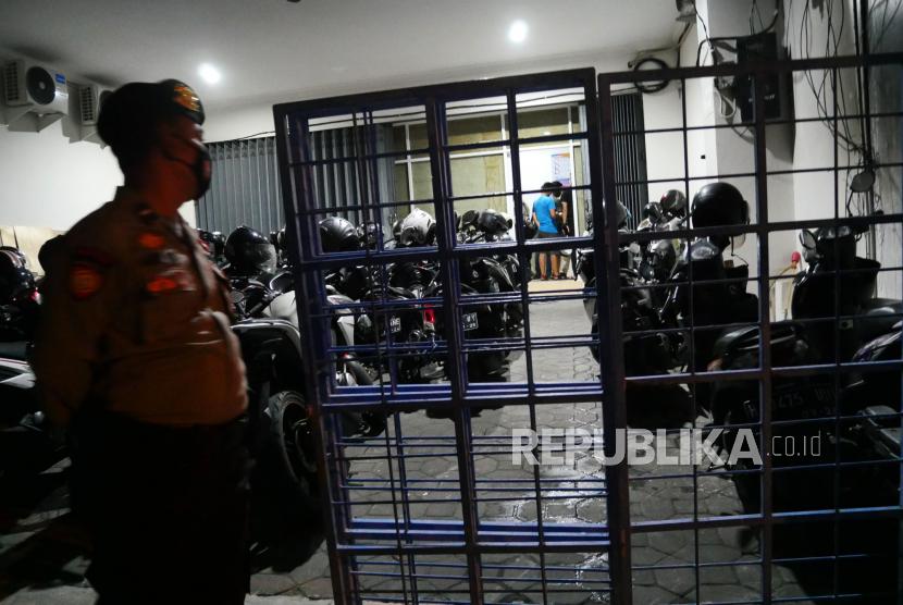 Polisi berjaga saat penggerebekan kantor pinjaman online ilegal di Samirono, Yogyakarta, Jumat (15/10) dini hari. Tim siber Ditreskrimsus Polda Jabar bersama Polda DIY berhasil menggerebek kantor pinjol ilegal. Sebanyak 86 orang berhasil diamankan, yang selanjutnya dibawa ke Jawa Barat. Selain itu, 105 buah komputer dan 105 telepon genggam juga diamankan dari penggerebekan ini.