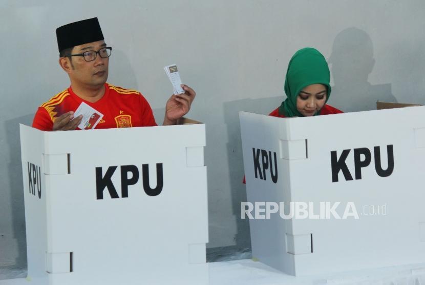 Calon Gubernur Jawa Barat Ridwan Kamil bersama istri Atalia Praratya melakukan pencoblosan dalam Pilkada Serentak 2018, di rumahnya, di Cigadung, Kota Bandung, Rabu (27/6).