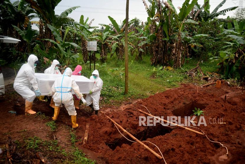 Petugas memakamkan jenazah pasien positif COVID-19 di lokasi pemakaman COVID-19 TPU Pasir Putih, Depok, Jawa Barat (21/6). Penyebaran dan penularan Covid-19 di Kota Depok, Jawa Barat mengalami peningkatan yang cukup drastis. Satgas Penanganan Covid-19 Kota Depok melaporkan pada Ahad (20/6) terjadi penambahan positif Covid-19 sebanyak 653 orang. Ini merupakan tertinggi kasus harian selama pandemi Covid-19. Prayogi/Republika.