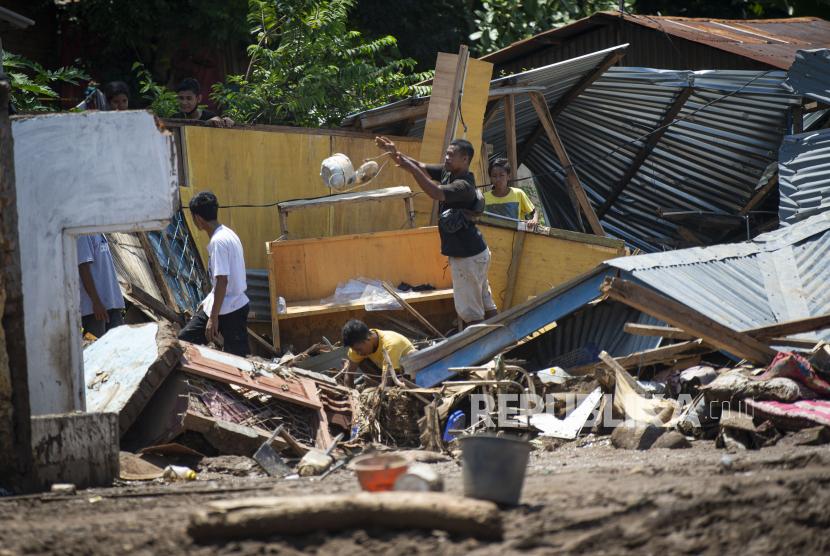 Sejumlah warga memindahkan barang-barang dari puing rumahnya yang hancur akibat banjir bandang di Adonara Timur, Kabupaten Flores Timur, Nusa Tenggara Timur (NTT), Rabu (7/4/2021).