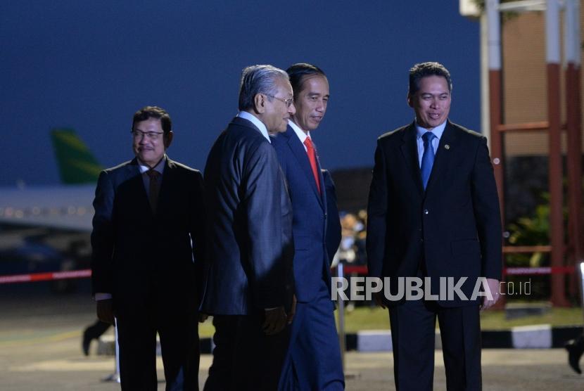 Kunjungan Kenegaraan PM Malaysia. Presiden Joko Widodo (tengah) bersama PM Malaysia Mahathir Mohamad saat tiba di Bandara Halim Perdanakusumah, Jakarta, Kamis (28/6).