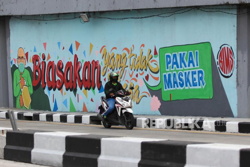 Pengendara motor melintas di dekat dinding bermural di terowongan Mayjen Sungkono, Surabaya, Jawa Timur. Tambahan kasus varian Delta baru ditemukan di Jawa Timur.