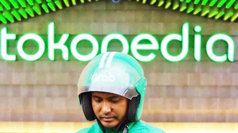 Seorang pengemudi Gojek berdiri di depan banner Tokopedia (Foto istimewa).