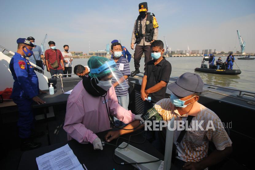 Petugas kesehatan memeriksa tekanan darah warga sebelum disuntik vaksin COVID-19 saat Vaksinasi Merdeka di atas kapal patroli Polairud Polda Jawa Timur di perairan Lumpur, Gresik, Jawa Timur, Selasa (3/8/2021). Direktorat Kepolisian Perairan dan Udara Polda Jawa Timur menggelar vaksinasi COVID-19 dengan sasaran nelayan dan masyarakat pesisir guna mewujudkan kekebalan kelompok atau