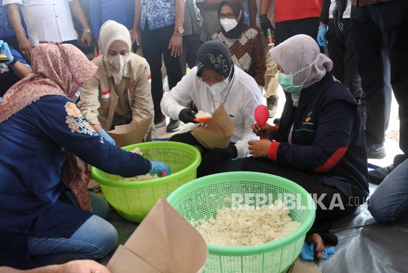 Menteri Sosial Tri Rismaharini (kedua kanan) didampingi Bupati Jember Faida membantu membungkus nasi saat mengunjungi posko banjir Desa Wonoasri di Tempurejo, Kabupaten Jember, Jawa Timur, Senin (18/1/2021).