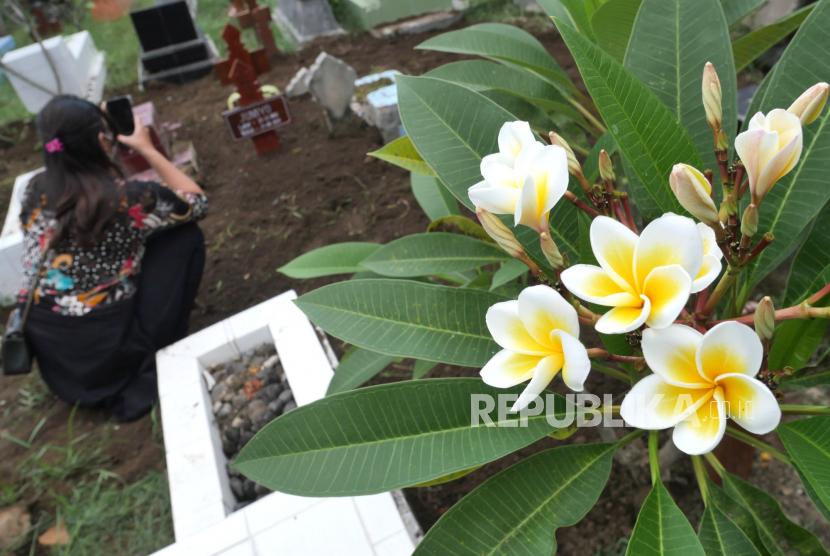 Kerabat keluarga memotret papan nisan usai pemakaman dengan protokol Covid-19 di Makam Ngeseng, Yogyakarta. Jumlah kematian akibat Covid-19 di Yogyakarta naik enam kali lipat selama Juli 2021.