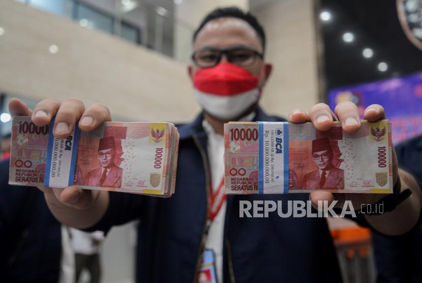 Petugas menunjukan uang palsu saat konferensi pers di Gedung Bareskrim Mabes Polri, Jakarta, Kamis (23/9). Bareskrim Mabes Polri mengunkap penangkapan 20 orang pelaku penyebar uang palsu yang terdiri dari tiga jaringan dengan barang sebanyak bukti 48 lak uang palsu jenis Dollar Amerika Serikat dan 110.138 lak uang palsu jenis rupiah.