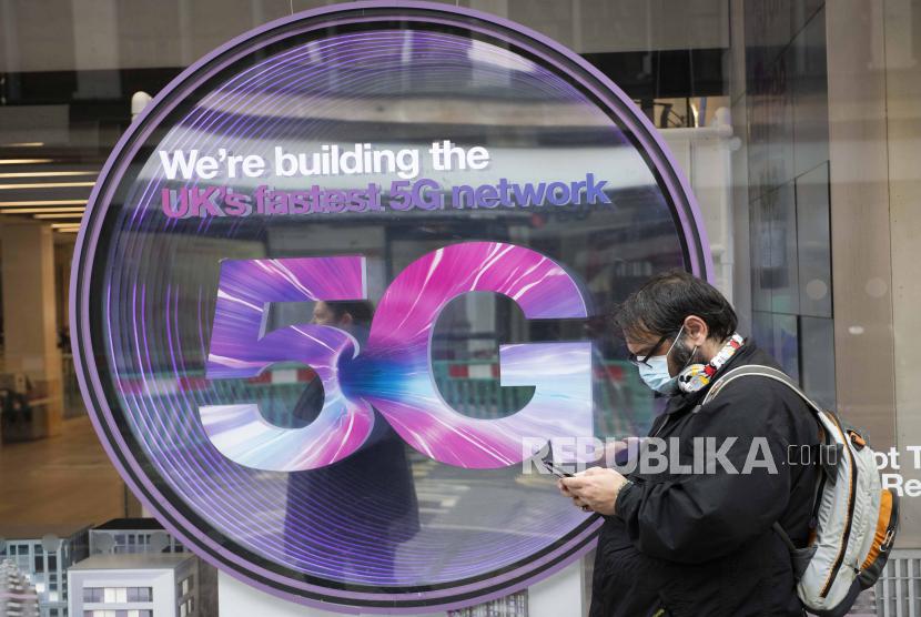 Seorang anggota masyarakat memeriksa teleponnya di luar sebuah toko ponsel yang menampilkan tanda 5G, Oxford Street, London. Jumat 12 Juni 2020.