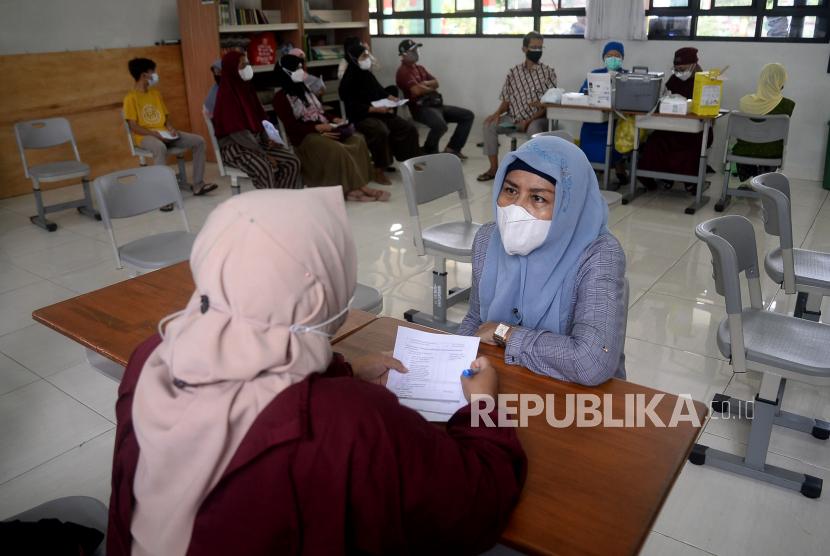 Tenaga kesehatan memeriksa kesehatan warga sebelum disuntikkan vaksin covid-19 Pfizer dosis pertama di SDN Kalibata 11, Jakarta, Selasa (14/9). Gubernur DKI Jakarta Anies Baswedan menyebutkan ada sekitar 2,5 juta warga pemilik kartu tanda penduduk (KTP) Jakarta belum mengikuti vaksinasi Covid-19. Sebagian besar warga Jakarta yang belum divaksinasi itu tidak mau karena berbagai alasan dan perlu pendekatan secara persuasif.Prayogi/Republika.