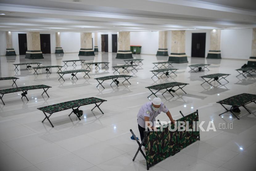 Petugas mengecek tempat tidur lipat untuk pasien OTG di Aula Masjid Hasyim Asyari, Jakarta Barat, Rabu (23/6). Sebanyak 100 tempat tidur lipat disiapkan di Aula Masjid Hasyim Asyari untuk dijadikan tempat isolasi mandiri pasien Covid-19 status Orang Tanpa Gejala (OTG), mengingat jumlah kasus harian Covid-19 di DKI Jakarta mengalami peningkatan beberapa hari terakhir. Republika/Thoudy Badai