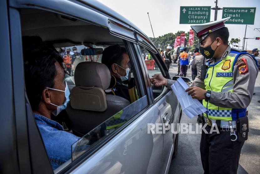 Petugas kepolisian memeriksa identitas pengemudi kendaraan dengan plat nomor dari luar Bandung di posko penyekatan larangan mudik di gerbang Tol Padalarang, Kabupaten Bandung Barat, Senin (10/5). Pada hari kelima penerapan larangan mudik Lebaran 2021, petugas gabungan di posko penyekatan larangan mudik Padalarang telah memutarbalikan sedikitnya 30 kendaraan berplat luar kota karena tidak memiliki surat kesehatan serta ijin perjalanan. Foto: Republika/Abdan Syakura