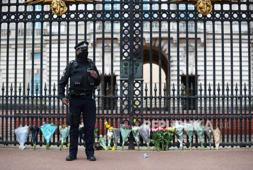 Seorang petugas polisi berdiri di samping karangan bunga di luar Istana Buckingham setelah diumumkan bahwa Pangeran Philip dari Inggris, suami Ratu Elizabeth, telah meninggal pada usia 99 tahun, di London, Inggris, 9 April 2021.