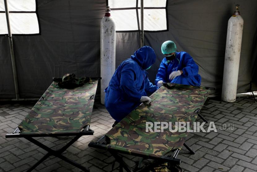 Tenaga kesehatan menyiapkan bed untuk pasien di tenda darurat khusus Covid-19.