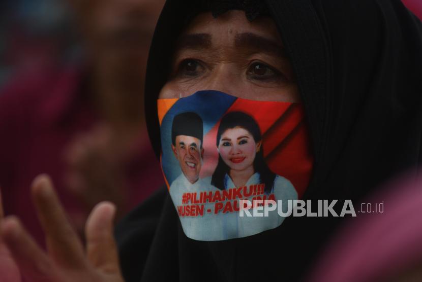 Simpatisan menggunakan masker bergambar pasangan bakal calon kepala daerah. Pemerintah dorong paslon PIlkada berkempanye dengan cara membagikan masker.
