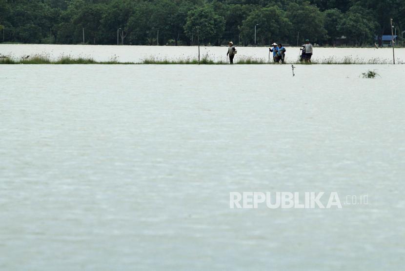 Petani melintasi area sawah yang terendam banjir di Widasari, Kabupaten Indramayu, Jawa Barat, Selasa (5/1/2021).