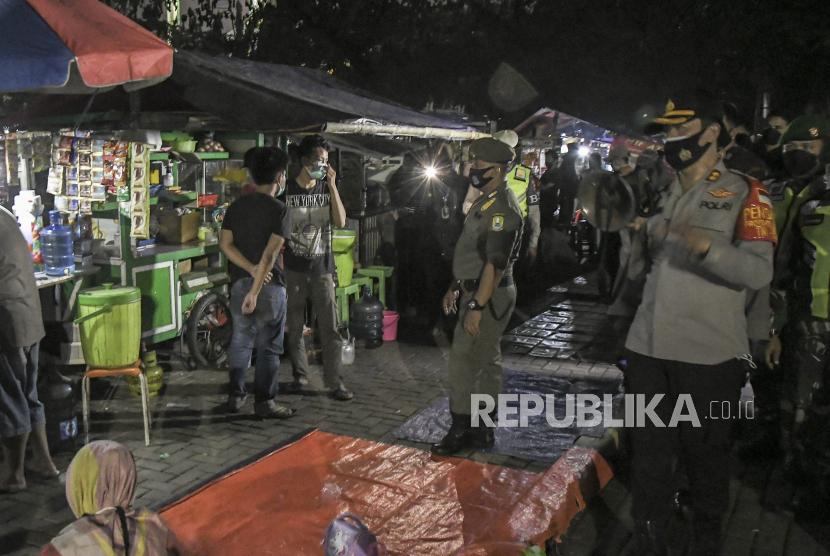 Sejumlah petugas gabungan dari TNI, Polri dan Satpol PP menghimbau pengunjung dan pedagang untuk patuh protokol kesehatan saat melaksanakan operasi Yustisi COVID-19 di Alun-alun Bekasi, Jawa Barat, Sabtu (19/6/2021). Operasi Yustisi di pusat keramaian tersebut bertujuan untuk menekan penyebaran wabah COVID-19.