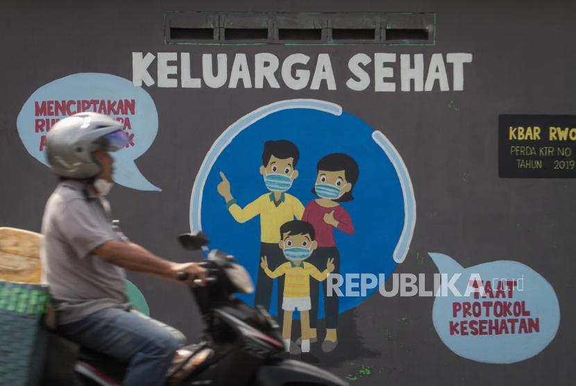 Pengendara melintas didepan mural bertema keluarga sehat di Ngemplak, Solo, Jawa Tengah, Rabu (14/7/2021). Berdasarkan hasil uji whole genome sequencing (WGS) dari 16 sampel yang dikirimkan Kota Solo ke laboratorium di Jawa Tengah semuanya menunjukan strain berkode B.1.617.2 atau varian delta, hal ini diperkirakan menjadi penyebab melonjaknya angka kasus COVID-19 di Kota Solo.