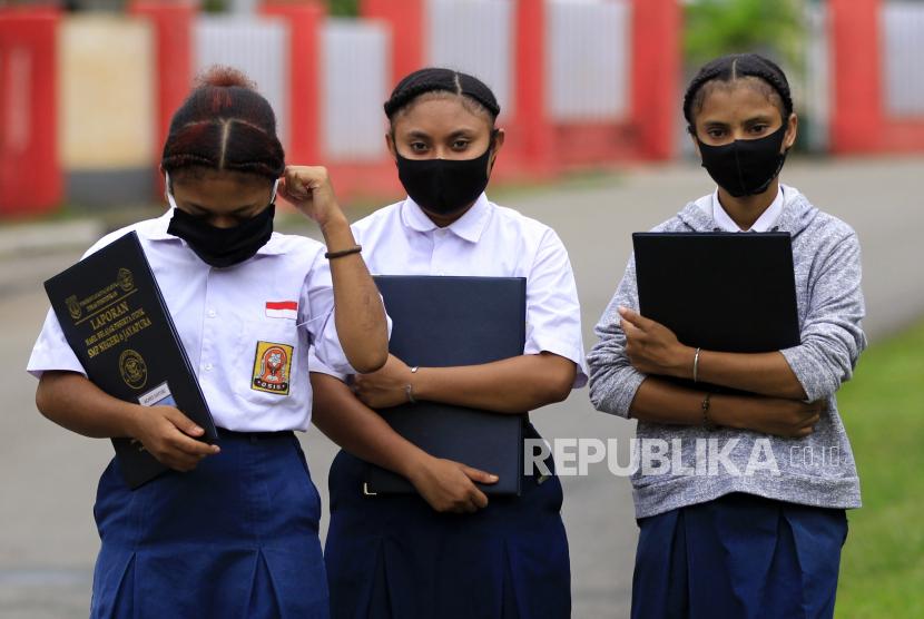 Siswa SMP Negeri 6 Jayapura dengan masker di wajahnya berjalan meninggalkan sekolah usai.
