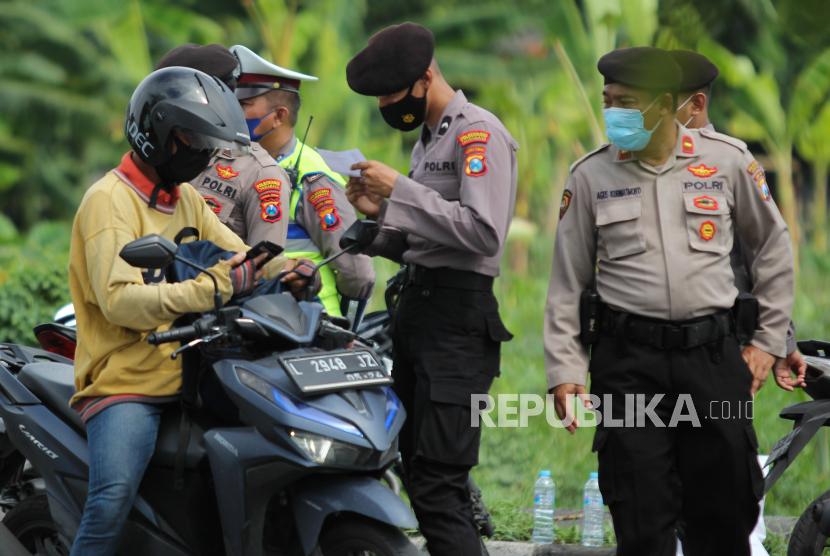Polisi memeriksa dokumen warga sebelum dilakukan tes Antigen saat penyekatan di akses masuk Jembatan Suramadu, Surabaya, Jawa Timur, Kamis (17/6/2021). Penyekatan dan tes Antigen dilakukan kepada warga yang akan menuju Pulau Madura melalui Jembatan Suramadu sebagai upaya memutus penyebaran COVID-19.