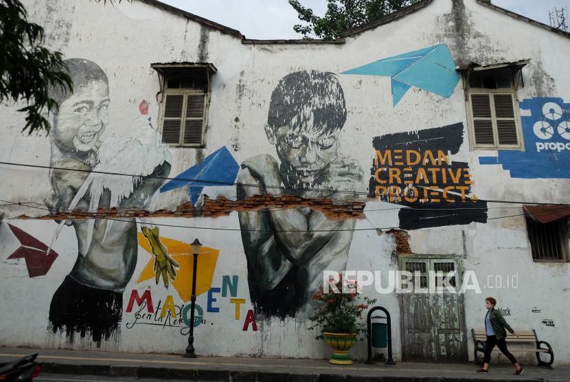 Warga melintas di depan mural di kawasan Kota Tua Kelurahan Kesawan, Medan, Sumatera Utara.