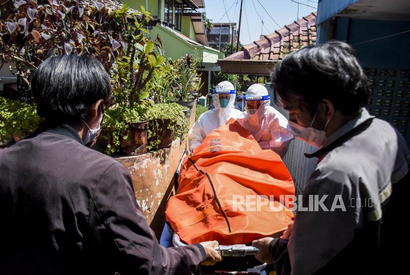 Petugas Public Safety Center 119 (PSC 119) bersama warga mengevakuasi jenazah pasien Covid-19 yang meninggal saat isolasi mandiri (isoman) di rumahnya di Jalan Padasuka, Cibeunying Kidul, Kota Bandung, Rabu (28/7). Berdasarkan hasil data yang dihimpun dari situs laporcovid19.org hingga (28/7) tercatat kasus kematian pasien Covid-19 saat isolasi mandiri dan di luar rumah sakit mencapai 2.705 kasus. Foto: Republika/Abdan Syakura