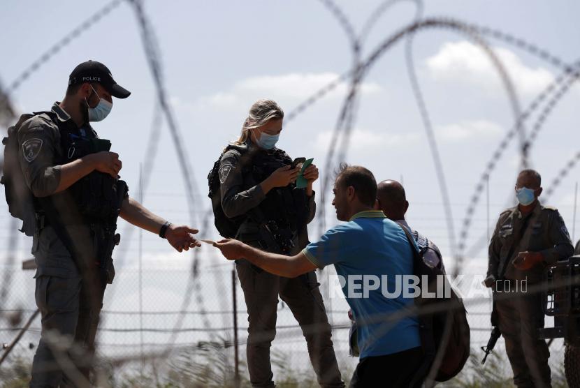 Pasukan keamanan Israel memeriksa identitas warga Palestina saat mereka mengantre dalam perjalanan kembali ke kota Jenin, Tepi Barat, melalui celah di pagar keamanan, dekat desa Israel Muqabla, 06 September 2021. Sejumlah tahanan keamanan melarikan diri dari Penjara Gilboa, demikian pernyataan Kantor Perdana Menteri Israel pada 06 September 2021.
