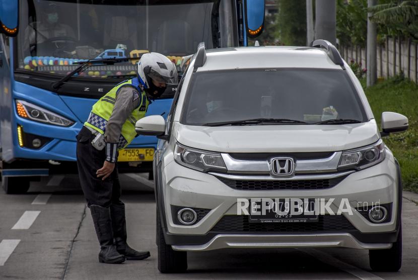 Anggota Satlantas Polresta Bandung memeriksa identitas serta surat keterangan sehat saat operasi penyekatan dan pemeriksaan di Gerbang Keluar Jalan Tol Soreang, Kabupaten Bandung (ilustrasi)