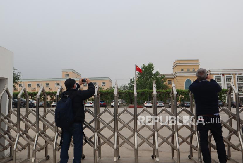 Sejumlah jurnalis asing memotret gedung perkantoran terpadu milik Pemerintah Kota Turban, Daerah Otonomi Xinjiang, China, Jumat (23/4/2021). Pemerintah China membantah klaim asing berdasarkan citra satelit yang menyebutkan  bahwa gedung tersebut merupakan penjara bagi warga dari kelompok etnis minoritas Muslim Uighur.