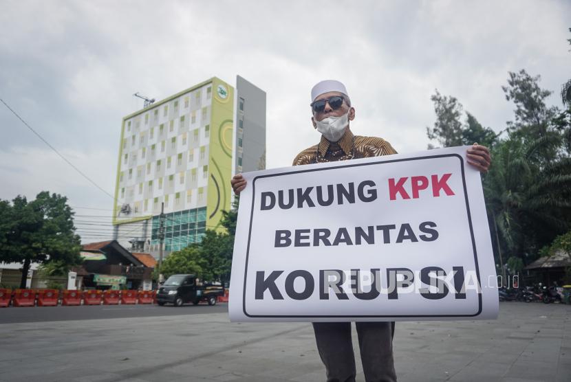 Pegiat sosial Hasan Mulachela melakukan aksi tunggal dengan mambawa poster dukungan kepada Komisi Pemberantasan Korupsi (KPK) di Manahan, Solo, Jawa Tengah, Senin (7/12/2020). Aksi tersebut sebagai bentuk dukungan terhadap KPK yang melakukan Operasi Tangkap Tangan (OTT) terhadap sejumlah pejabat Kementerian termasuk menteri yang terlibat kasus korupsi.