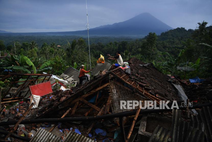 Warga mengumpulkan barang berharga miliknya di antara reruntuhan rumah yang rubuh akibat gempa di Desa Kali Uling, Lumajang, Jawa Timur, Ahad (11/4/2021). . Sekitar ratusan rumah warga di wilayah itu rusak akibat gempa bermagnitudo 6,1 SR yang terjadi di Kabupaten Malang pada Sabtu (10/4).