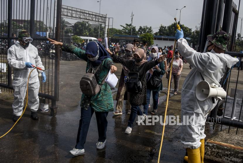 Sejumlah warga disemprot cairan disinfektan sebelum memasuki stadion untuk menjalani vaksinasi Covid-19 di Stadion Gelora Bandung Lautan Api (GBLA), Gedebage, Kota Bandung, Kamis (17/6). Sedikitnya 5.000 warga se-Bandung Raya mengikuti vaksinasi massal Covid-19 yang digelar oleh TNI, Polri dan Pemerintah Kota Bandung. Foto: Republika/Abdan Syakura