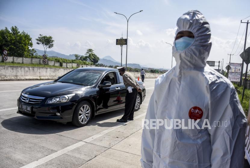 Petugas kepolisian memeriksa identitas dan surat keterangan sehat dari pengemudi kendaraan dengan pelat nomor luar Bandung saat operasi ppkm mikro di gerbang keluar Tol Soreang, Kabupaten Bandung, Ahad (20/6). Penyekatan dan pemeriksaan tersebut merupakan tindak lanjut dari status wilayah Bandung Raya siaga satu Covid-19 serta ditujukan untuk menekan mobilitas kendaraan agar tidak masuk ke wilayah Bandung Raya demi mencegah penyebaran Covid-19. Foto: Republika/Abdan Syakura