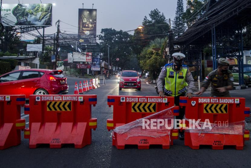 Anggota kepolisian menutup akses jalan Perbatasan menuju Kota Bandung dari Kabupaten Bandung Barat-Subang  di kawasan Ledeng, Bandung, Jawa Barat, Ahad (18/7/2021). Penjagaan akses menuju Kota Bandung di kawasan perbatasan terus dilakukan selama PPKM Darurat guna mencegah penyebaran COVID-19 dan mengantisipasi lonjakan mobilitas warga untuk antispasi mudik dan wisata jelang Hari Raya Idul Adha 1442 Hijriah.
