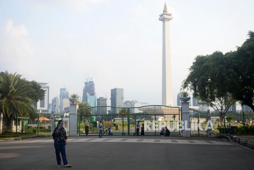 Warga berfoto di luar pagar Monumen Nasional (Monas), Jakarta, Sabtu (15/5). Pada libur Lebaran 2021 kawasan Monas masih ditutup untuk pengunjung karena penerapan Pemberlakuan Pembatasan Kegiatan Masyarakat (PPKM). Hal itu membuat sejumlah warga harus menelan kekecewaan lantaran terlanjur datang dan hanya bisa berfoto dari luar pagar tanpa bisa bisa masuk ke dalam.Prayogi/Republika.