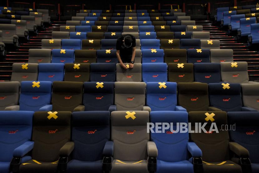 Petugas merapikan tanda jarak pada kursi penonton di studio bioskop.