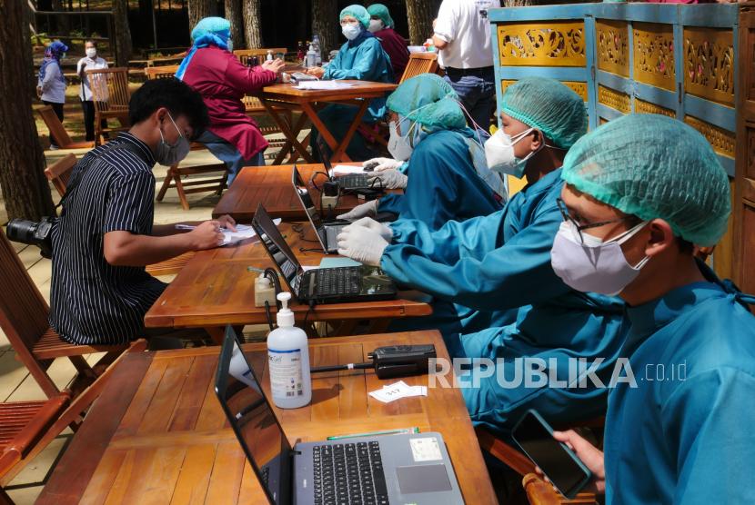 Tenaga kesehatan melakukan screening sebelum melaksanakan vaksinasi.