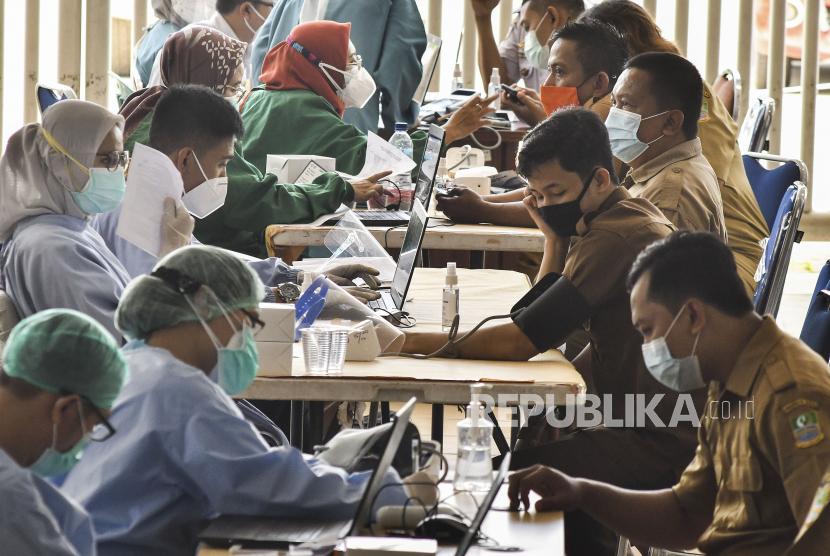Sejumlah Aparatur Sipil Negara (ASN) melakukan cek kesehatan sebelum mengikuti vaksinasi COVID-19 di Stadion Wibawa Mukti, Cikarang, Kabupaten Bekasi, Jawa Barat, Senin (1/3/2021). Menurut data Dinas Kesehatan Kabupaten Bekasi, sebanyak 5.360 pegawai unit pelayanan publik mengikuti vaksinasi COVID-19 yang dilakukan selama dua hari.